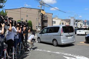 報道陣に囲まれ、向日町署を出る橋本容疑者を乗せた車(向日市上植野町)