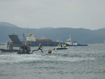 土砂を積んだ台船を止めるためカヌーをこぐ市民と、拘束しようと飛び込む海上保安官=13日、名護市辺野古・K8護岸近く