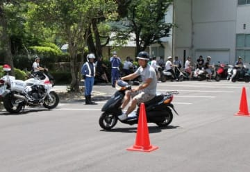 コーンの間を抜け、適切な運転方法を確かめる学生