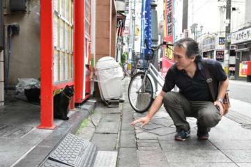 手術を終えた猫を見つめる中央通商店街振興会の岩崎会長。ボランティアグループがえさ場やトイレを管理し猫を見守っている