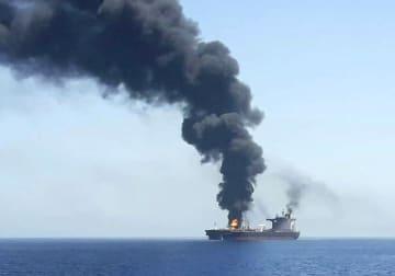 13日、ホルムズ海峡付近で攻撃を受け、オマーン湾で煙を上げるタンカー(国営イラン放送提供・AP=共同)