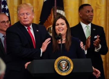 米ホワイトハウスで、サンダース大統領報道官(中央)に寄り添うトランプ大統領=13日、ワシントン(ロイター=共同)