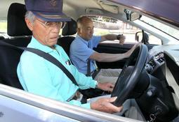 教官(奥)からアクセルとブレーキの踏み方を教わる男性=小野自動車教習所
