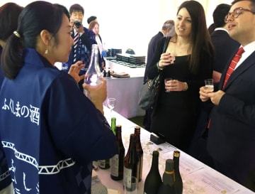 13日、ベルギーのブリュッセルで開かれたEU日本政府代表部のパーティーで、振る舞われた福島県の日本酒を楽しむ出席者ら(共同)