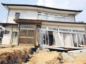 東日本大震災の揺れによる地割れで全壊した民家=2011年3月30日、仙台市青葉区折立5丁目