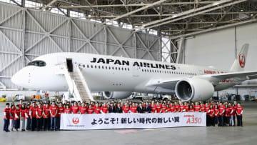 日航のエアバスA350初号機が羽田空港に到着し、格納庫で写真に納まる関係者=14日午前
