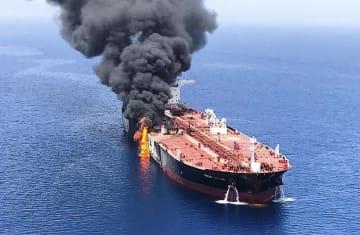 13日、ホルムズ海峡付近で攻撃を受けて火災を起こし、オマーン湾で煙を上げるタンカー。2隻が攻撃を受けたが、いずれのタンカーかは不明(AP=共同)