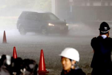 人工的に再現した1時間に300ミリの豪雨で、見通しが悪い中を走行する乗用車=14日午後、茨城県つくば市の防災科学技術研究所