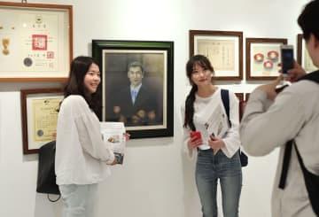 14日、ソウルで開かれた写真展で、李秀賢さんの肖像画とともに記念撮影する大学生(共同)