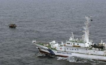 日本海で北朝鮮漁船とみられる木造船(左)に退去警告する海上保安庁の巡視船=5月(海上保安庁提供)