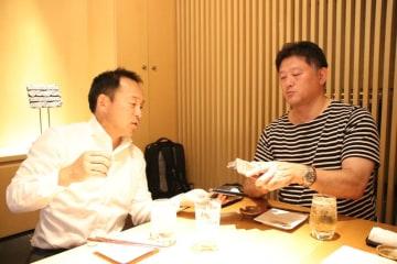 スマホで昔の写真を交換する永友洋司さん(左)と今泉清さん