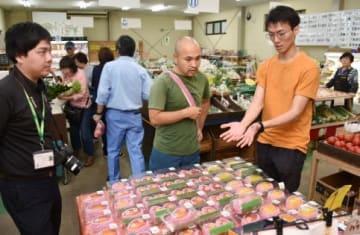 農園の直販店で素材を吟味する花輪剛さん(中央)=11日、大崎町