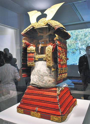 館内に展示されている赤糸威鎧 兜・大袖付(複製)=上写真=と前庭にある富永氏が制作したブロンズ像