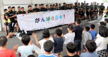 児童から贈られた横断幕を掲げるラグビー日本代表=14日午前、宮崎市・シーガイアスクエア1