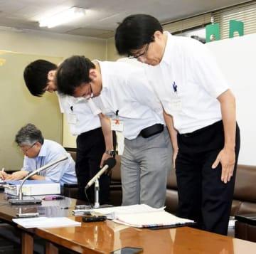 記者会見で頭を下げる上場課長(右端)