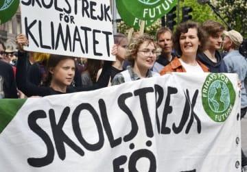 スウェーデン・ストックホルムで、温暖化対策を求める抗議デモに参加するグレタ・トゥンベリさん(左端)=5月24日(共同)
