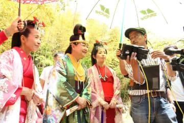 撮影した映像を見ながら、田中正照監督(右)と演技を確認する出演者たち=4月21日、小城市小城町畑田の星巌寺