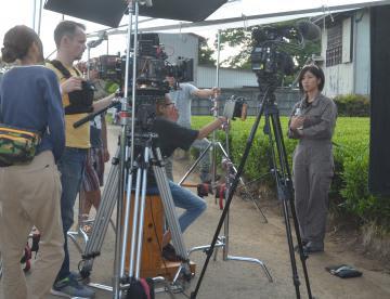 米国の番組制作会社の取材で、さしま茶の歴史や特徴などを紹介する石山奈幹さん(右)=境町