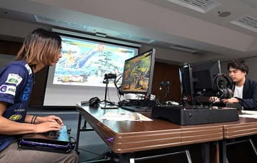 格闘ゲームでプロゲーマー(左)と対戦する研究会の参加者=12日、大阪市中央区の大阪商工会議所