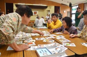 読み上げられた取り札を取ろうとする参加者ら=鹿屋市の高隈地区交流促進センター