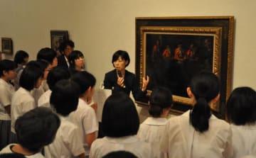 開幕したルオー展で、学芸員によるギャラリートークに耳を傾ける来場者=15日午前、宮崎市・県立美術館