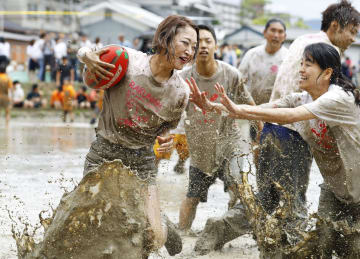 水田でラグビーを楽しむ「田んぼラグビー」で、泥だらけになってプレーする女性ら=16日、京都市