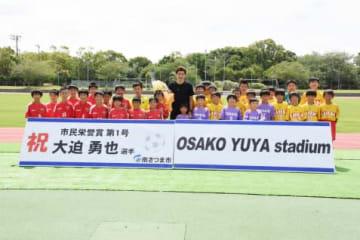 市民栄誉賞を受け、子どもたちと記念撮影する大迫勇也選手(中央)=16日、南さつま市の「OSAKO YUYA stadium」