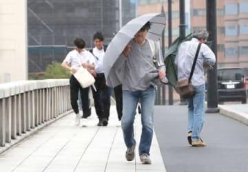 強風の中、萬代橋を歩く人たち=16日午後3時すぎ、新潟市中央区