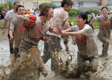 水田で泥だらけになりながらラグビーを楽しむ参加者たち(京都市伏見区)