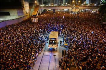 An ambulance is pictured surrounded by thousands of protesters dressed in black during a new rally against a controversial extradition law proposal in Hong Kong on June 16, 2019. Photo: Hector Retamal/AFP.