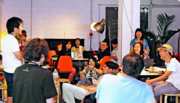 ITを活用した課題解決で、発表者(左端)の報告を笑顔で聞くイベントの参加者=9日、沖縄市中央のスタートアップ・ラボ・ラグーン