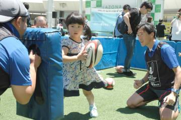 ラグビーボールを持ったプレーに挑戦する子どもたち =川崎市幸区のラゾーナ川崎広場