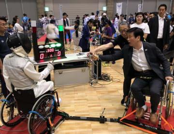 車いすフェンシングを体験する森田健作知事(右)=16日、千葉市美浜区の幕張メッセ