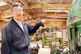 1500トン油圧機など自社が誇る機械と技術を説明する石岡常務取締役