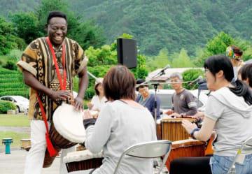 モフランさん(左)の手ほどきで打楽器演奏を楽しむ参加者