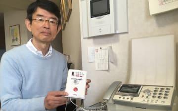 特殊詐欺対策に有効な迷惑電話防止機器を手にする本田さん=横浜市中区(画像の一部を修整しています)