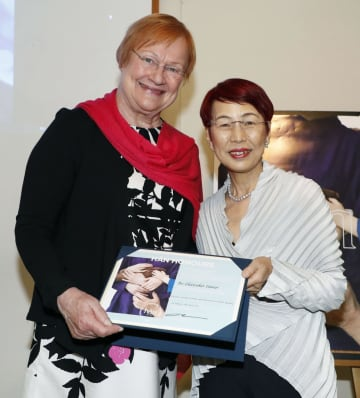 フィンランド外務省から感謝状を贈られ、同国初の女性大統領となったタルヤ・ハロネンさん(左)と記念撮影する社会学者の上野千鶴子さん=17日午前、東京都港区