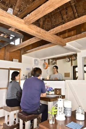 「山のCafeランプ」でお客と談笑する松野友美さん(右)。見上げるとかやぶき屋根の裏側が見える=上越市板倉区猿供養寺