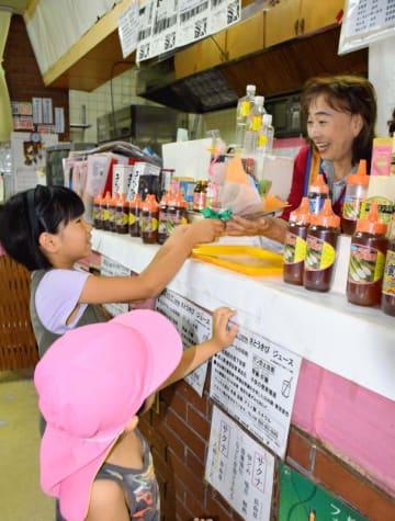 常連客の新垣海梨さん(左)から花束をもらった照屋悦子さん