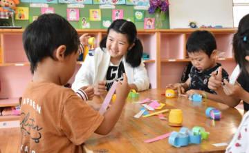 七夕飾りの制作を一緒に楽しむ園児と児童