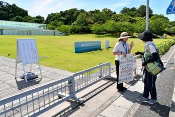 停電による臨時休館を来館者に説明する職員=横須賀美術館
