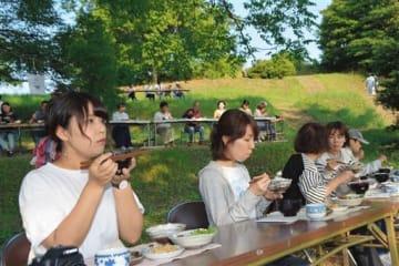 「宇土飯を喰らう会」が宇土城跡で開いた朝食会で、段々になった斜面で食事する参加者=宇土市