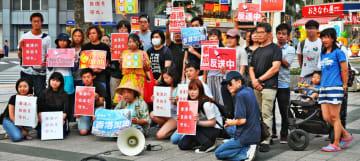 香港にエールを送ろうとプラカードを持って声を上げる大学生有志ら=16日、那覇市の県民広場