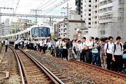 駅間で緊急停止したJR神戸線の快速電車から線路に下り、元町駅まで歩く乗客=2018年6月18日午前、神戸市中央区