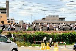 大阪府北部地震の発生後、JR神戸線の西宮-さくら夙川間で電車が緊急停止し、線路を歩く乗客たち。大半の鉄道が一斉に運休し、通勤や通学に大きな影響が出た=2018年6月18日午前、西宮市西福町