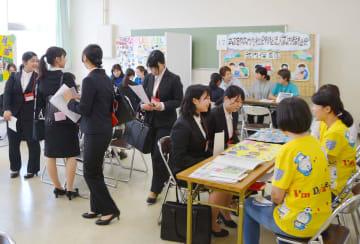 各ブースで保育の仕事内容を尋ねる学生たち=佐賀市の佐賀女子短期大学