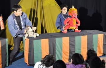 【人形劇団「どむならん」の公演を楽しむ児童(手前)ら=津市一身田のフレンテみえで】