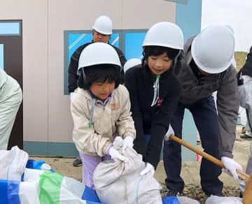 土のう積みに参加する子どもたち