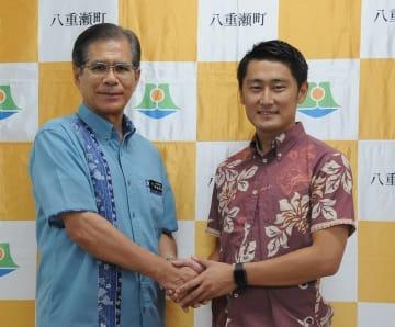 八重瀬町での練習拠点整備を発表した新垣安弘町長(左)と三上昴社長=八重瀬町役場