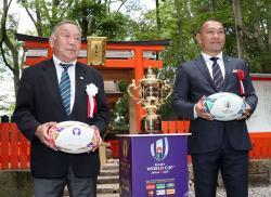 ラグビーW杯成功祈願の集いで、エリス杯の横に立つ坂田会長(左)と元木さん=京都市左京区・下鴨神社